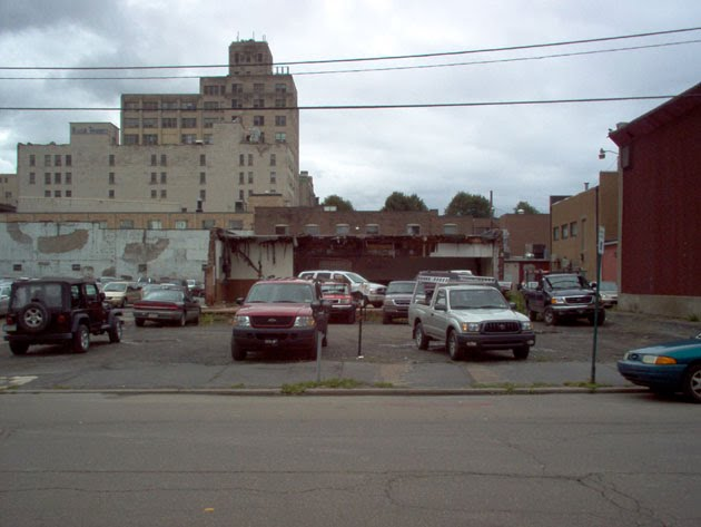 Several slightly better-looking cars in front of same half-demolished building
