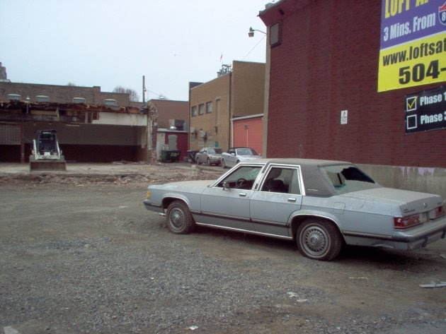 Lone busted-up car in front of half-demolished building