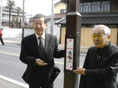 Two really old guys unveiling street lamps festooned with moe.
